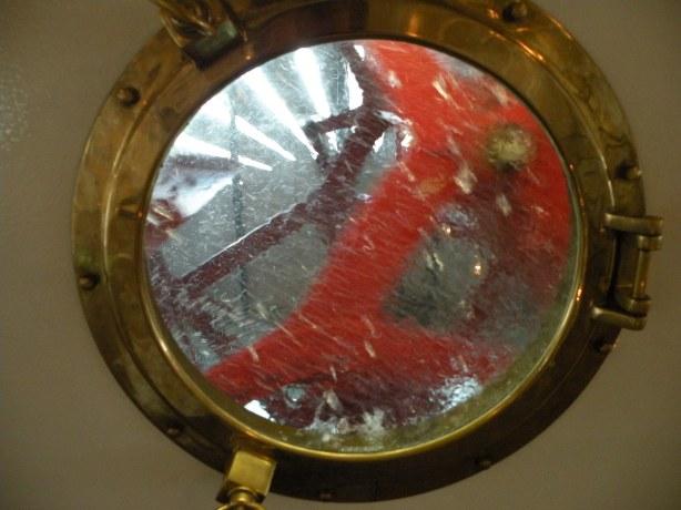 Prin hublou, pe puntea de jos a vaporului, se vad zbaturile in miscare