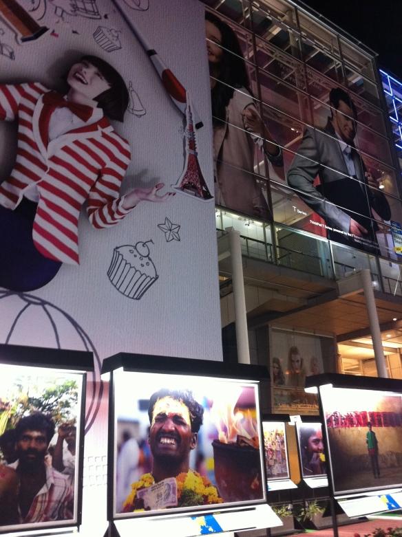 De jos in sus: primul strat: expozitie de fotografie in aer liber; al doilea: Reclama cu fata imbracata in jacheta cu dungi albe si rosii; al treilea strat: vitrine la intrarea in mall-ul ce se vede pe fundal; al patrulea (sus spre dreapta): reclame pe fatada mall-ului.
